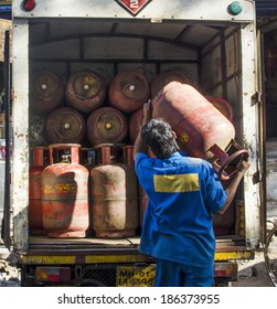 Mumbai, India - February 17, 2014 - Worker delivering LPG gas cylinders into the truck for customers