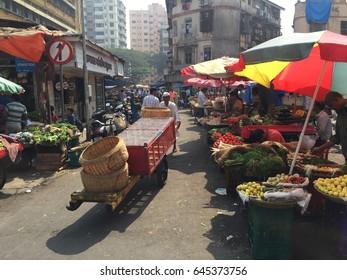 Mumbai, India - February 2, 2016 : local people walking and push goods cart along narrow lane at local fresh market selling fruits and vegetables