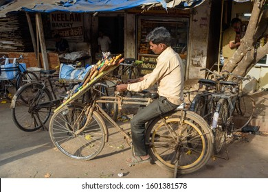 Mumbai, India - February 26, 2019: Indian man sharpens knives on cycle in street on machine in Dharavi Slum
