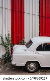 Mumbai, India - February 5, 2018: A white Hindustan Ambassador Indian taxi car waiting in front of a striped wall on a side street in the suburb of Worli