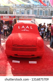 Mumbai, India - February 8, 2019:  An art installation of an ambassador car coated with kumkum - a red powder made from turmeric used for social and religious markings, at  Kala Ghoda Arts Festival