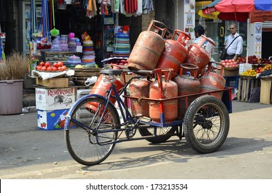 MUMBAI, INDIA - JAN 24, 2014 -  loadful of LPG gas cylinders on tri rickshaw to be delivered to customers in local local market
