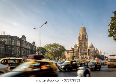 Mumbai, India - January 10th 2016 - Gothic building in downtown Mumbai with a taxi car in the front ground. Late afternoon sky with some light clouds in the sky. Mumbai, India, Asia.