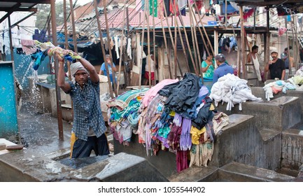 MUMBAI, INDIA - JANUARY 12, 2016: Indian worker washing clothes at Dhobi Ghat, open air laundromat in downtown of Mumbai in Maharashtra State