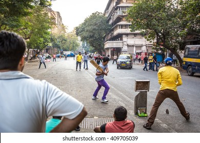 Mumbai, India - January 12th 2016 - Big group of young people playing cricket in the streets of downtown Mumbai in India.