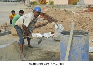 Mumbai, India - January 16, 2014 - worker mixing cement at construction site in Mumbai