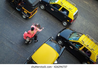 MUMBAI, INDIA - JANUARY 5, 2014: Indian man riding a bike with a woman on the rack waiting for the moment to join traffic.