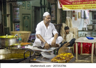 Mumbai, India - July 3, 2014 -  Muslim man frying snack in hot oil pan from stall at crowded Mohammad Ali Road in the evening during Ramzan fasting month
