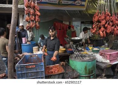 Mumbai, India - July 3, 2015 : Muslim male vendors selling halal foods masala grilled tandoori chicken and meats  from roadside stall at night market during holy month of Ramadan Ramazan