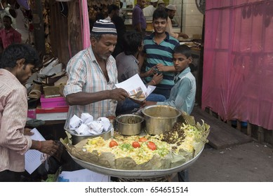 Mumbai, India - July 3, 2015 : Muslim male vendors selling halal foods and snacks from roadside stall at night market during holy month of Ramadan