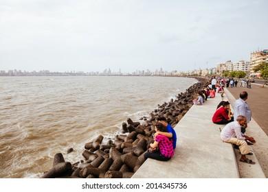 Mumbai, India - July 30 2017: People enjoy life sitting and walking along Marine Drive and promenade in Colaba, Mumbai, India