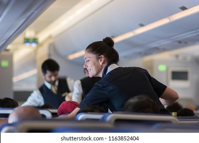 Mumbai, India - July 8, 2018 - Flight attendants speaking with a passenger sitting in the economy class of the route Munich - Mumbai of Lufthansa Airlines.