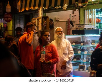 Mumbai, India - June 01, 2019 : Old Muslim male vendors selling sweets at roadside stall at night market in holy month of Ramadan Ramazan at Bhendi Bazar