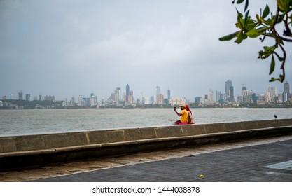 Mumbai, India - June 30, 2019 : Unidentified couple taking photos / selfie with Mobile at Marine Drive promenade