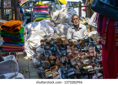 Mumbai, India - Mar-2019: An Indian man selling foot wears on streets of Mumbai India. The streets shops offer cloths and accessories at bargain prices.