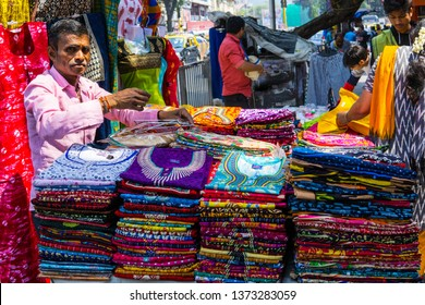 Mumbai, India - Mar-2019: An Indian man selling suits and ladies night wears on the streets of Dadar west area in Mumbai, these street shops offer cloths and accessories at bargain prices.
