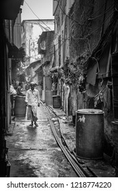 Mumbai, India- March 22 2017: Man walking  in an alley in Dharavi, the third largest slum in Asia.