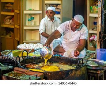 Mumbai, India - May 11, 2019 : Muslim male vendors cooking selling halal foods and snacks fried pancake Malpuas from roadside stall at night market in holy month of Ramadan Ramazan at Bhendi Bazar