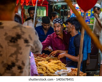 Mumbai, India - May 11, 2019 : Muslim male vendors cooking selling halal foods from roadside stall at night market in holy month of Ramadan Ramazan at Bhendi Bazar