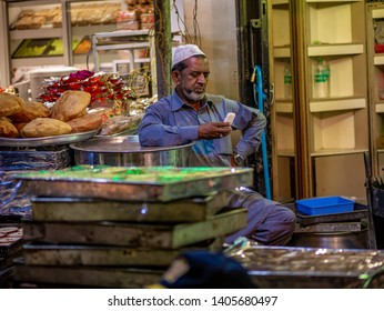 Mumbai, India - May 11, 2019 : Muslim male vendors talking on mobile phone from roadside stall at night market in holy month of Ramadan Ramazan at Bhendi Bazar