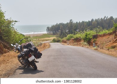 Mumbai / India - May 23 2018: A parked motorcycle on a road leading to the ocean on a hot afternoon