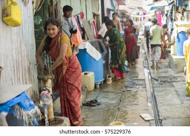 MUMBAI, INDIA - NOV 13: Unidentified woman is pumping water from well in slum November 13, 2013 in Mumbai, India. People in slum have limited access to clean water.