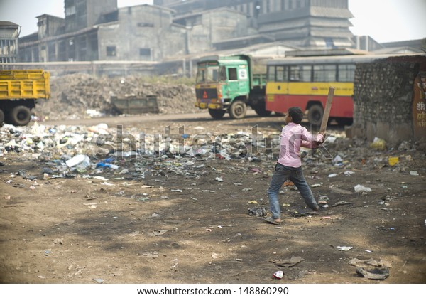 MUMBAI, INDIA - NOV 13: Unidentified child is playing cricket next to a garbage disposal area in a slum on November 13, 2012 in Mumbai, India. Over 60% of population lives in slums in Mumbai.