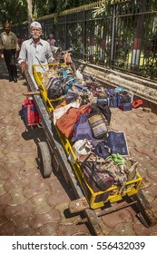 MUMBAI, INDIA - NOVEMBER 10, 2016: A dabbawala, or lunchbox delivery worker, located just outside the Mumbai train station has a full handcart of lunches ready to deliver through the city streets.
