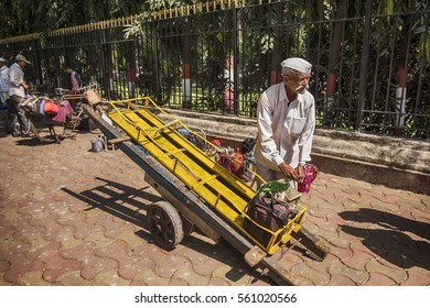 MUMBAI, INDIA - NOVEMBER 10, 2016: In Mumbai, a dabawalah, or lunchbox delivery worker, starts to fill his handcart with lunches for his clients on the sidewalk outside the Churchgate railway station.