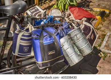 MUMBAI, INDIA - NOVEMBER 10, 2016: A bicycle is fully loaded with lunchboxes in bags and cans ready to be be delivered through the streets of Mumbai by the dabbawalla delivery service.