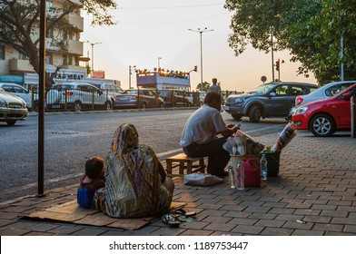 Mumbai, India - November 11, 2016: Indian man with a family sitting on the pavement and selling roses in the street in Mumbai, India