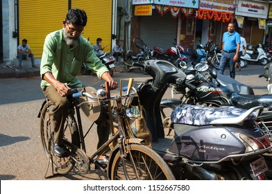 Mumbai, India - November 13, 2016: Older Indian man sharpening a knife on his home made bicycle grinder right in the street.