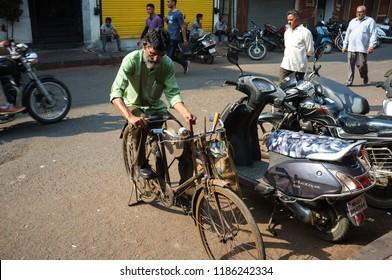 Mumbai, India - November 13, 2016: Older Indian man sharpening a knife on home made bicycle grinder in Mumbai, India