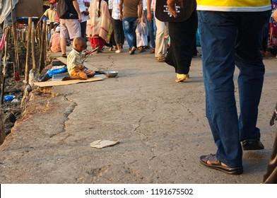 Mumbai, India - November 13, 2016: People walking along a poor homeless boy near Haji Ali mosque in Mumbai India