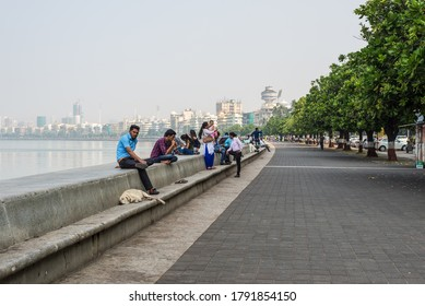 Mumbai, India - November 22, 2019: People rest on the Marine Drive - A famous landmark in Mumbai attracted by many tourist visiting India.