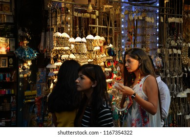 Mumbai, India - November 4 2017: Girl picking a necklace and other jewellery on a shopping/market street in Bombay