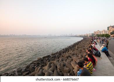 MUMBAI, INDIA - November 5 2017: Locals watch the sunset on Marine Drive on a hot summer's evening in Mumbai, India