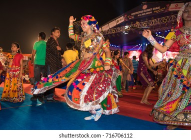 Mumbai, India - October 16, 2015 - Female dancers  in traditional colorful Indian costume on the floor among crowd during Navratri (nine-day) dance Festival