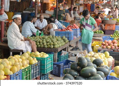Mumbai, India - October 19, 2015 - Indian trader in his shop on local market selling pineapple and other goods