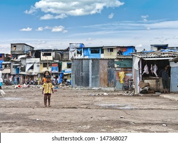 MUMBAI, INDIA - SEPTEMBER 13: Some unidentified children are playing on a blank area of a slum infront of their homes on September 13, 2008 in Mumbai, India. Beside a butcher is waiting for customers.