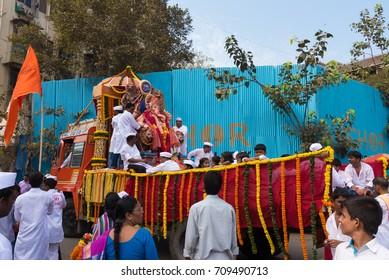 Mumbai, India - September 20, 2015 : Devotees bringing Lord Ganesha for procession in colorful vehicle during Hindu Lord Ganesha chaturathi festival along the street