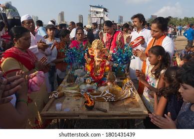 Mumbai, India - September 23, 2018 : Devottes praying chanting to Lord Ganesh idol to be immersed in the Arabian sea during Hindu  Ganesha chaturathi festival
