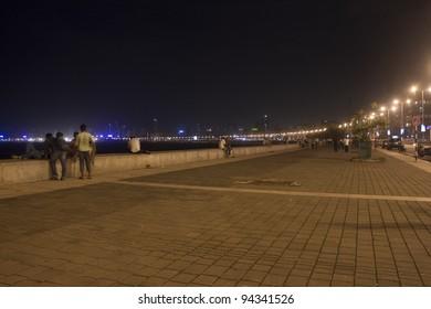 MUMBAI, INDIA - SEPTEMBER 5: Unidentified people walk on Marine Drive on September 5, 2011 in Mumbai, India. Marine Drive is a 3-kilometre-long boulevard in South Mumba. It is a road along the coast.