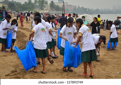 MUMBAI, INDIA-19 September 2013:a group of unidentified young students helping one another to clean up the Chaupati Beach in south Mumbai after Hindu festival of immersion of Ganesha into the sea ends