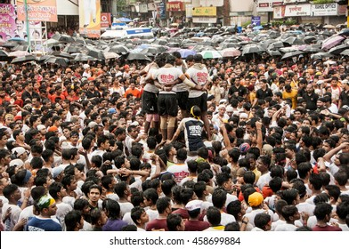 MUMBAI, MAHARASHTRA- INDIA - 22 AUGUST 2015 : Group of young men building of human tower, to catch and break the pot filled with butter, on day of celebration of hindu festival Janmashtami in india.