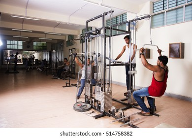 MUMBAI, MAHARASHTRA, INDIA, 3 MAY 2016 : Unidentified young men working out on fitness equipment at gym.