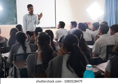 MUMBAI, MAHARASHTRA, INDIA, 6 APRIL 2017 : Unidentified group of engineering Students study with university professor  in modern school classroom.