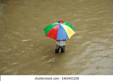 Mumbai; Maharashtra; India- Asia; Aug; 2011 : Man walking in Deep water with Colourful Umbrella during heavy rains water logging flooded street near Hindmata, Parel.