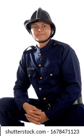 Mumbai; Maharashtra; India- Asia; Dec. 26; 2009 - Male model studio shot Indian young caucasian handsome and strong fireman in uniform wearing helmet on head white background
