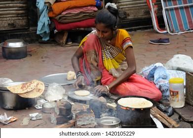 Mumbai; Maharashtra; India- Asia; Jan; 2017: Homeless Indian poor woman living on footpath cooking bread or chapati on footpath at princess street kalbadevi bombay
